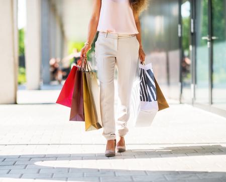Close-up op jonge vrouw met boodschappentassen op het winkelcentrum steegje