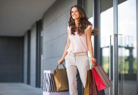 Mujer joven con bolsas de compras caminando hacia fuera de la tienda