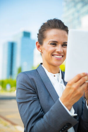 topicality: Happy business woman using tablet pc in office district Stock Photo