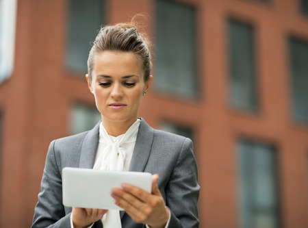 person woman: Business woman using tablet pc in front of office building Stock Photo