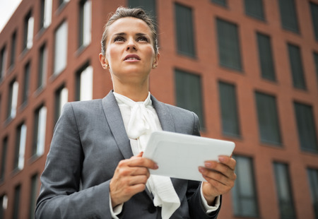 topicality: Portrait of serious business woman with tablet pc in front of office building
