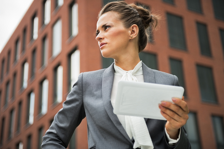 topicality: Serious business woman with tablet pc in front of office building
