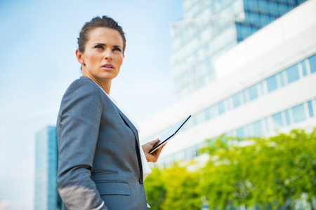 topicality: Portrait of confident business woman with tablet pc in office district