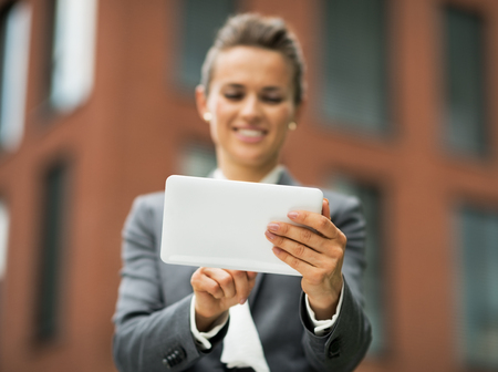 Closeup on business woman using tablet pc in front of office building