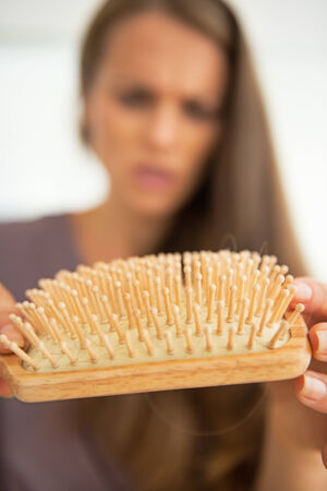 disquieted: Closeup on concerned woman looking on hair comb Stock Photo