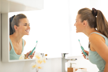 Young woman looking in mirror after brushing teeth Stock Photo