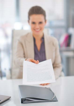 business report: Closeup on happy business woman giving document