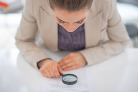 suspiciousness: Business woman exploring document with magnifying lens Stock Photo