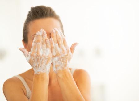 若い女性の浴室で顔を洗う
