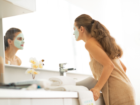 Young woman with facial cosmetic mask looking in mirror in bathroom photo