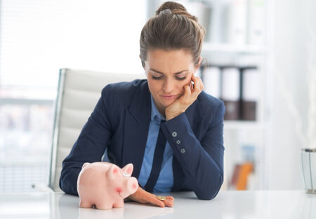 thrift box: Portrait of sad business woman with piggy bank looking on coin Stock Photo