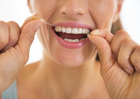 Primer en la mujer joven que usa la seda dental