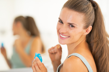 oral care: Portrait of happy young woman with dental floss Stock Photo