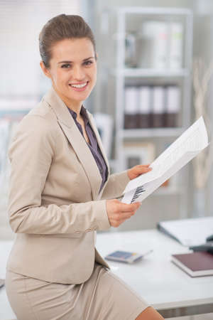 Mujer de negocios feliz que trabaja con documentos en la oficina Foto de archivo
