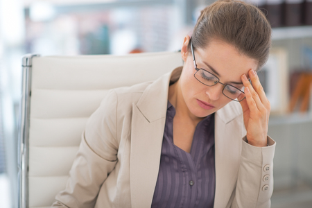 Portrait of stressed business woman with eyeglasses in office photo