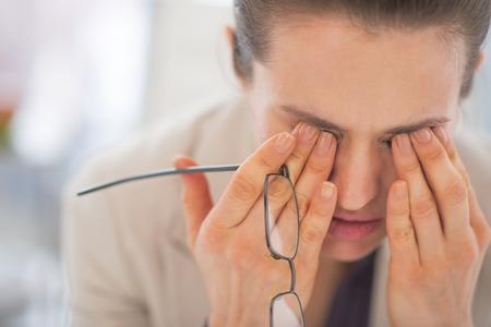 Retrato de mujer de negocios cansado con gafas en la oficina Foto de archivo