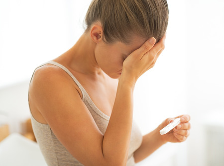prueba de embarazo: Mujer joven frustrada con la prueba de embarazo Foto de archivo