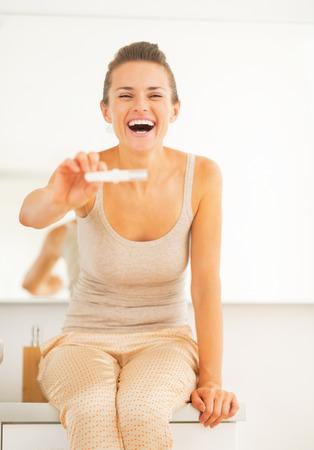 Happy young woman showing pregnancy test photo
