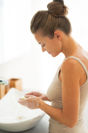 hygienics: Young woman washing hands in bathroom Stock Photo