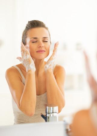 Fiatal nő mosás arc a fürdőszobában