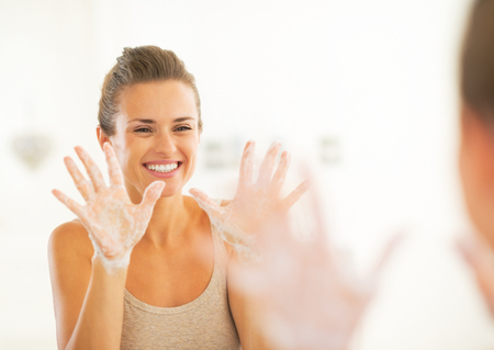 soapy: Happy young woman showing soapy hands