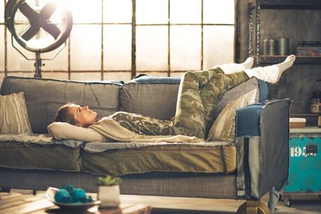Pihentető fiatal nő feküdt tetőtéri lakás Stock fotó