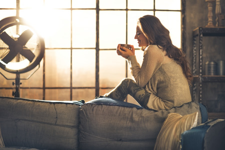 Young woman enjoying cup of hot beverage in loft apartment Stockfoto