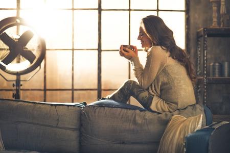 Mujer joven disfrutar de una taza de bebida caliente en el apartamento tipo loft