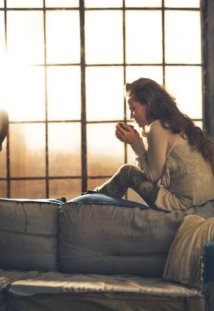 Junge Frau genießen Tasse heißes Getränk in Loft-Wohnung