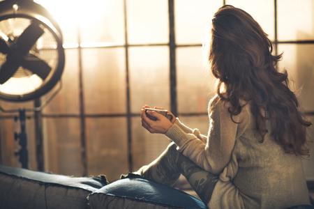 relajado: Mujer joven disfrutar de una taza de bebida caliente en el apartamento tipo loft. vista trasera