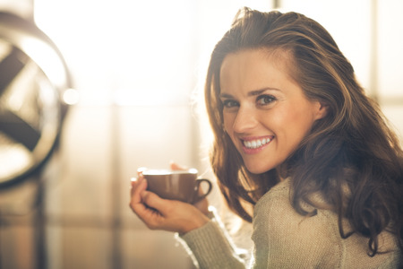warm drink: Portrait of happy young woman with cup of hot beverage