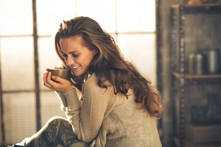 tea house: Portrait of relaxed young woman with cup of coffee in loft apartment Stock Photo