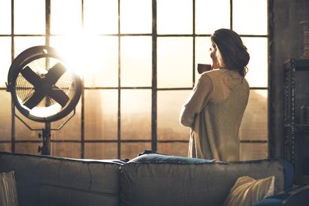 Mujer joven disfrutar de una taza de café en el apartamento tipo loft. vista trasera Foto de archivo