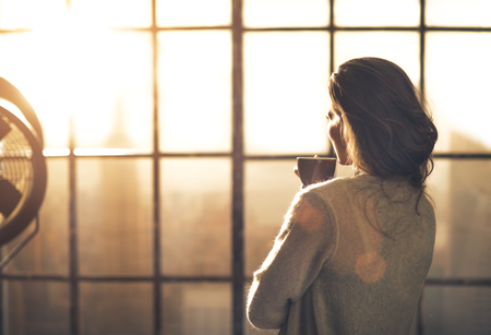 Jonge vrouw genieten van een kopje koffie in de loft appartement. achteraanzicht Stockfoto