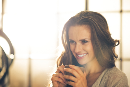 Portrait of smiling young woman with cup of coffee Stock Photo