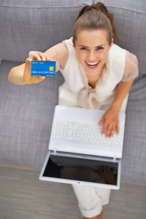 topicality: Happy young woman with laptop showing credit card