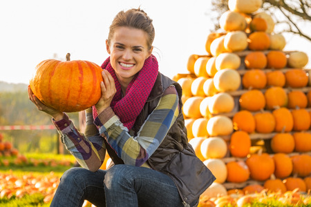 Portrait of happy young woman sitting with pumpkin in front of pumpkin piramide