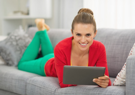Smiling young woman laying on couch with tablet pc photo