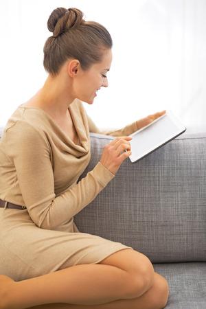 divan: Mujer joven que usa la PC de la tableta mientras est� sentado en el div�n