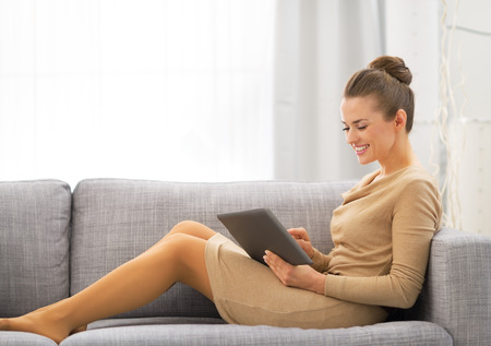 topicality: Young woman sitting on sofa and using tablet pc Stock Photo