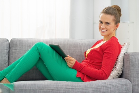 topicality: Young woman sitting on divan and using tablet pc