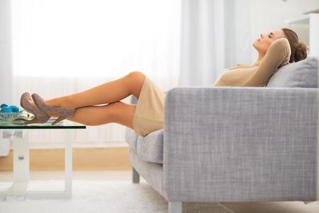 divan: Ama de casa joven Relaxed que pone en el div�n en el sal�n