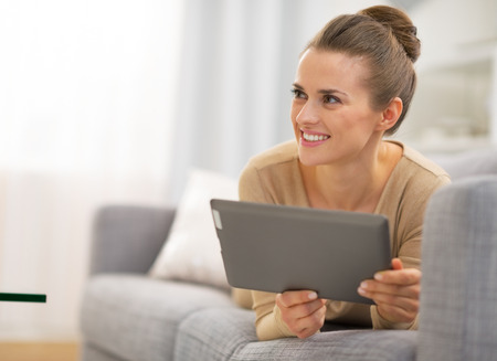 topicality: Thoughtful young woman laying on couch and using tablet pc
