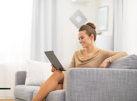 topicality: Happy young woman sitting on divan and using tablet pc Stock Photo