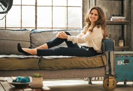divan sofa: Happy young woman sitting on sofa in loft apartment Stock Photo