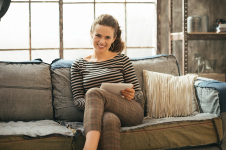 topicality: Happy young woman with tablet pc sitting in loft apartment