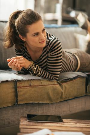 divan: Junge Frau, die auf Couch in der Loft-Wohnung
