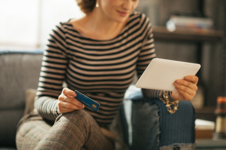 topicality: Closeup on young woman with credit card and tablet pc