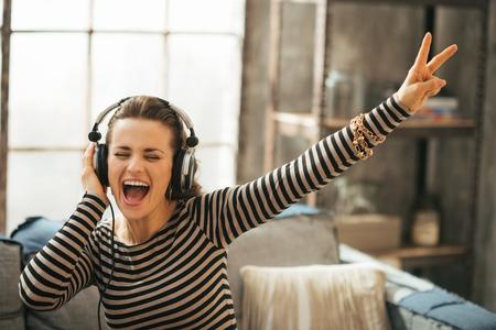 Vrolijke jonge vrouw luisteren muziek in de koptelefoon in de loft appartement