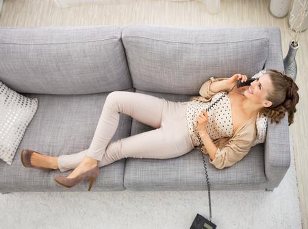 divan: Junge Frau, die auf Couch in Wohnzimmer und Telefon spricht